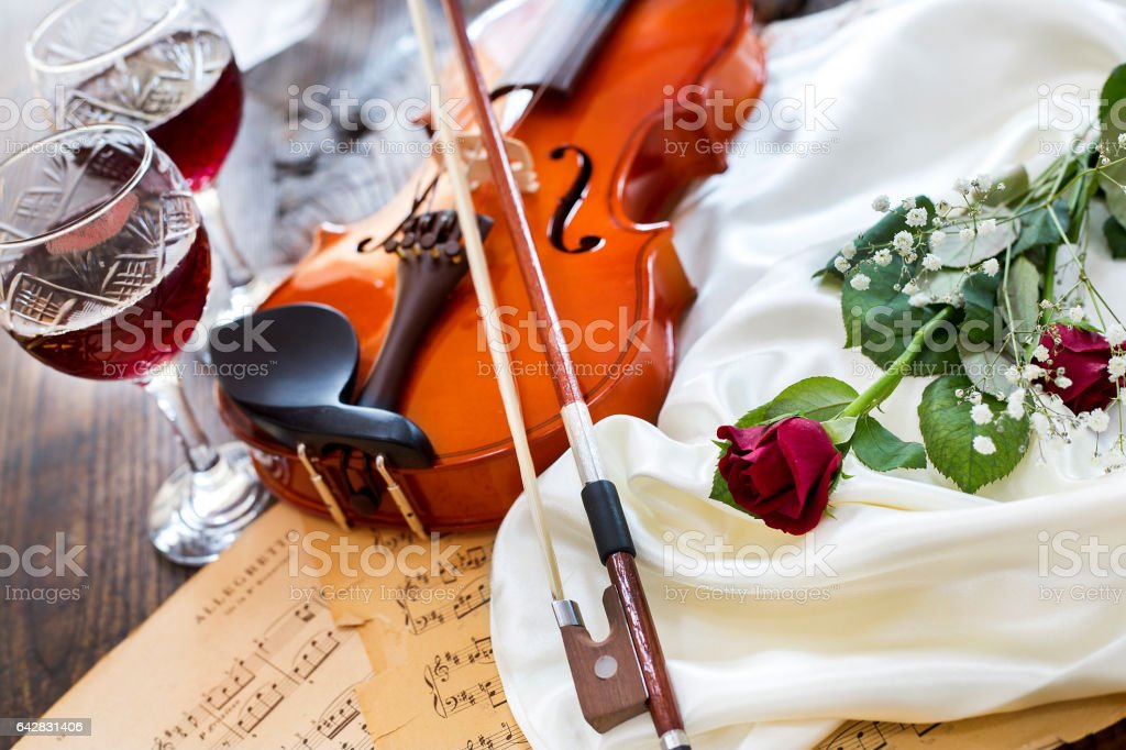 Violin, red rose, wine and music notes on satin fabric stock photo