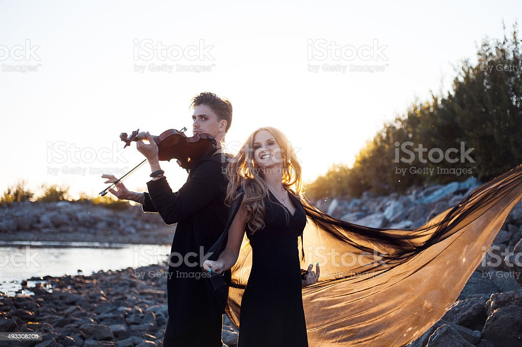 violinist and his Muse,   young man plays on the background stock photo