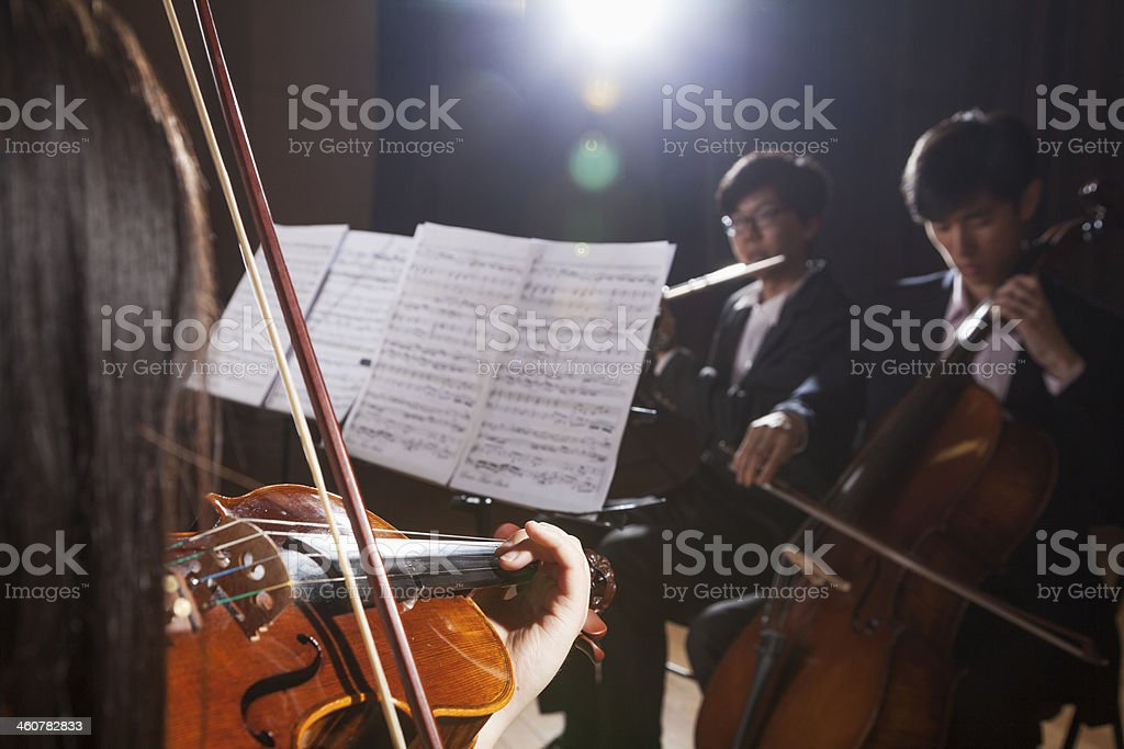 Violinist and other musicians playing during a performance, lens flare stock photo