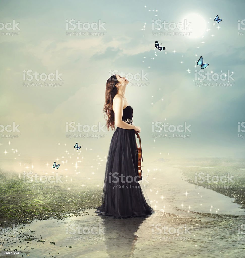 Violinist at a brook under the moon light stock photo