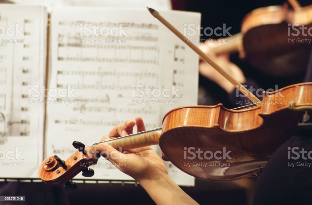 Violinist playing in orchestra close up stock photo