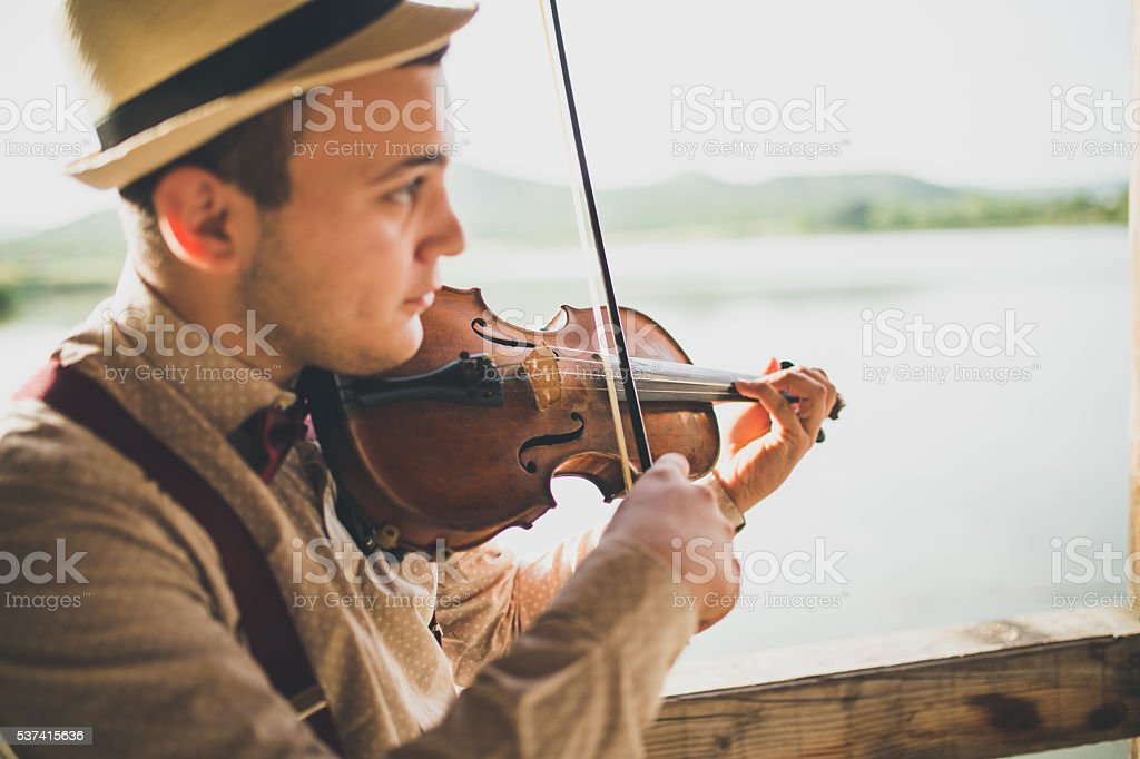 Violinist playing the violin by the lake stock photo