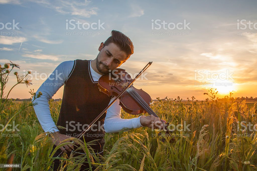 Violinist playing violin at the sunset stock photo