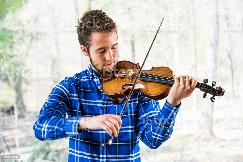 Violinist practising in front of a window stock photo