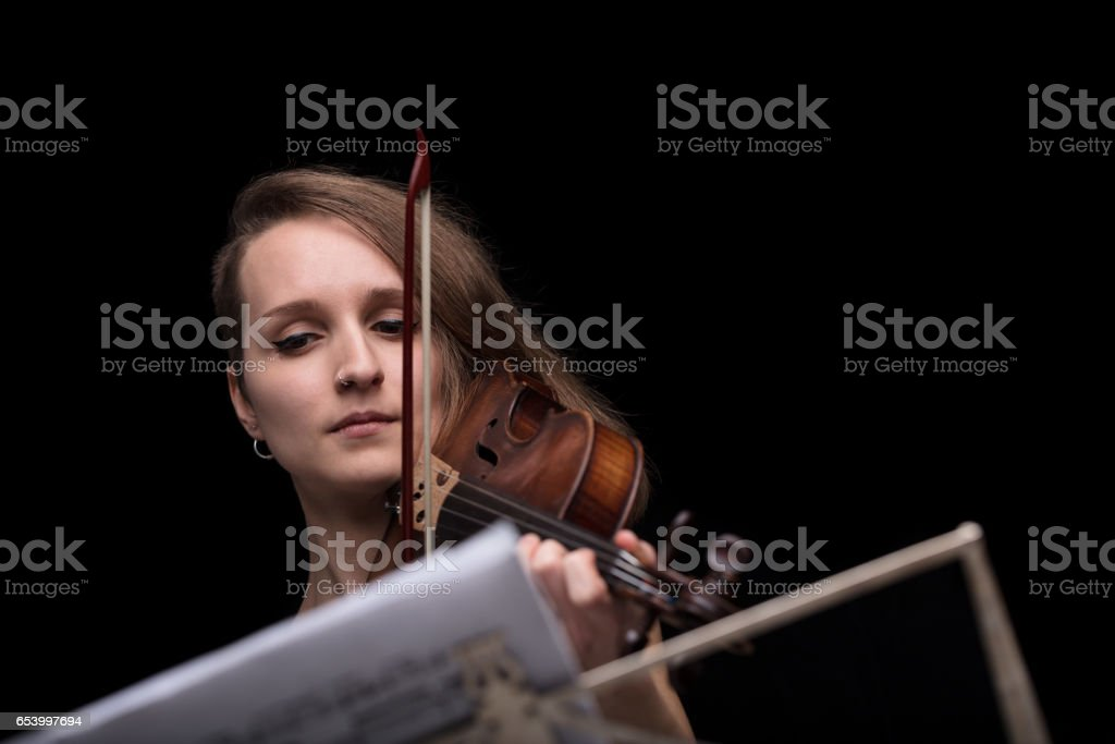 violinist reading music score and playing stock photo