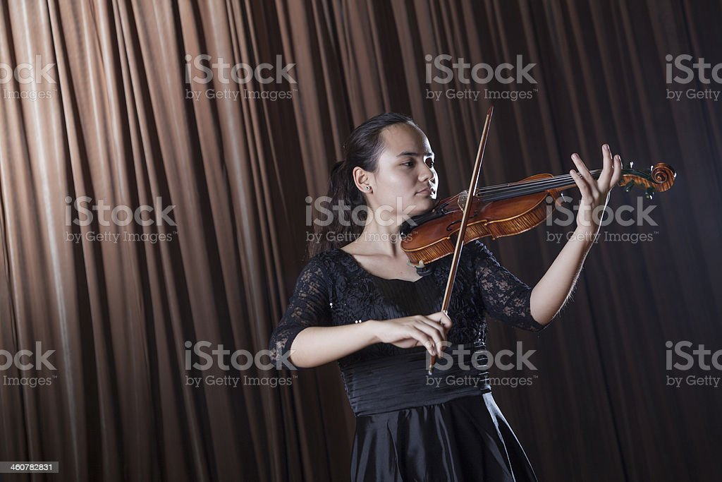 Violinist standing and playing the violin at a performance stock photo
