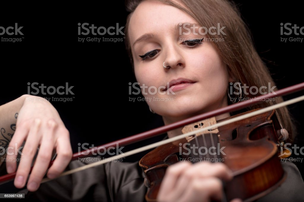 violinist woman with a nose piercing playing stock photo