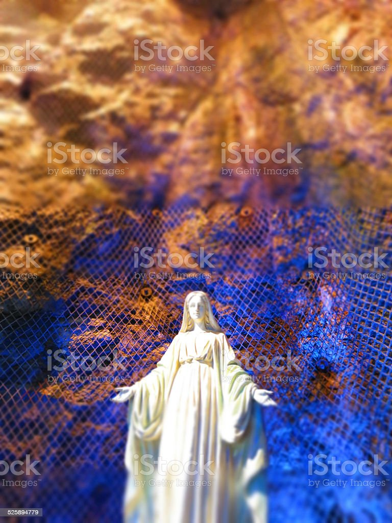 Virgin Mary Statue with Blue Light Underground with Fence stock photo
