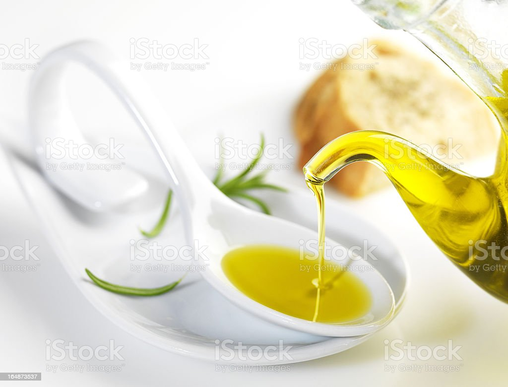 virgin olive oil pouring in a spoon stock photo
