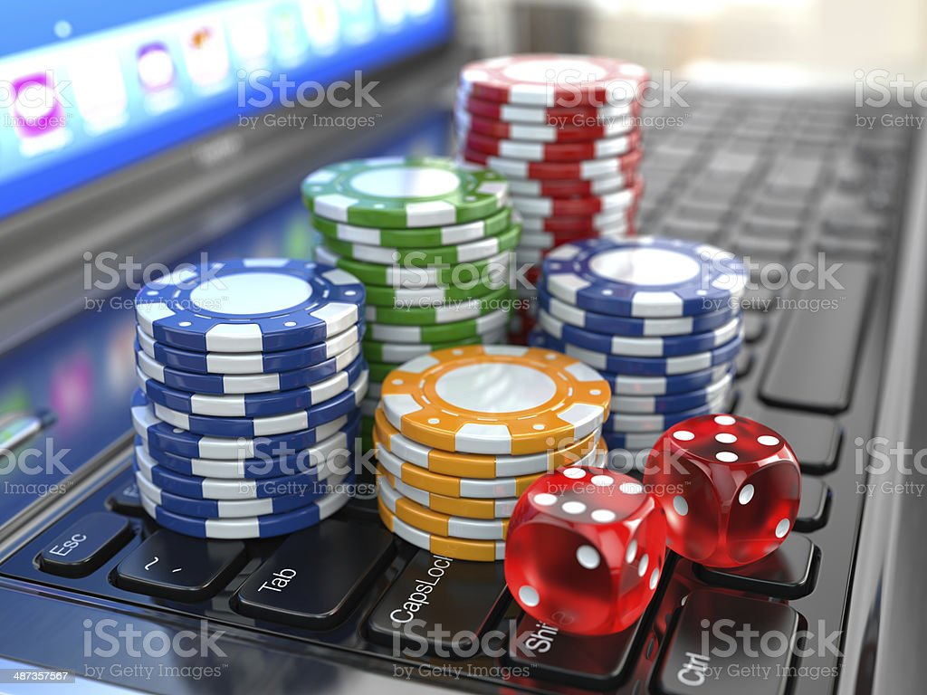 Virtual casino. Online gambling. Laptop with dice and chips. stock photo