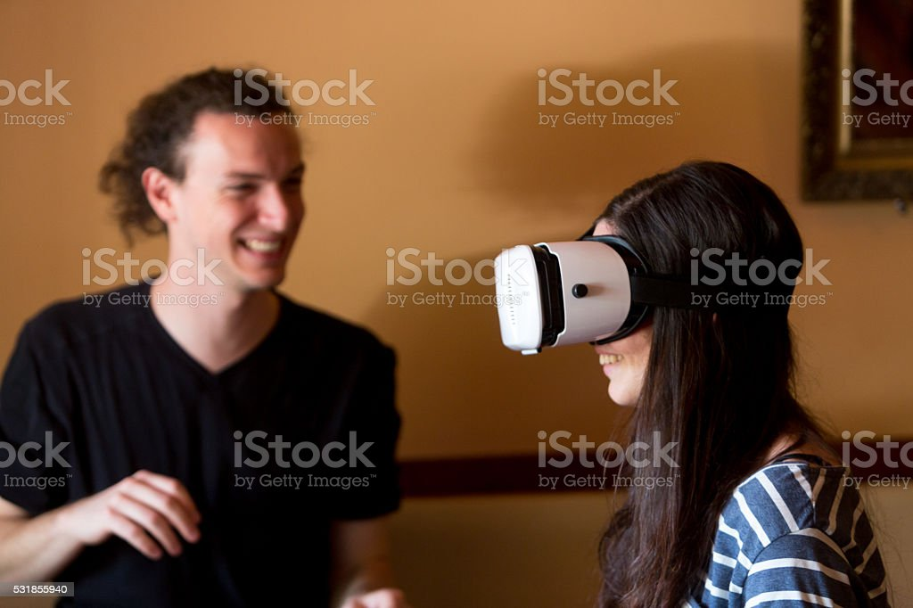 Virtual reality game. Girl using head mounted display with pleasure....