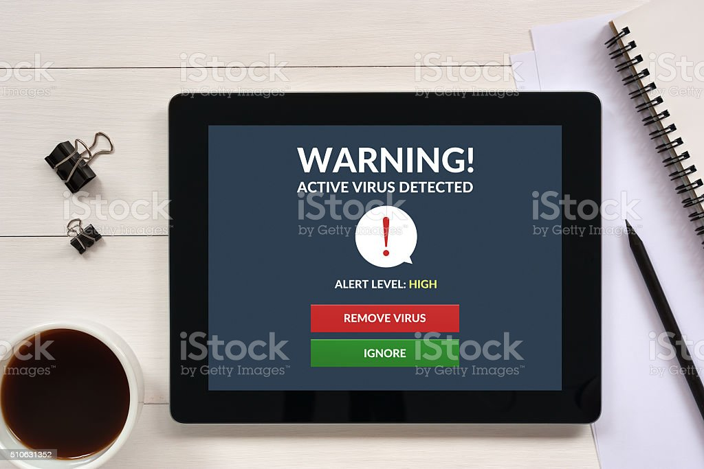 Virus alert on tablet screen with office objects stock photo