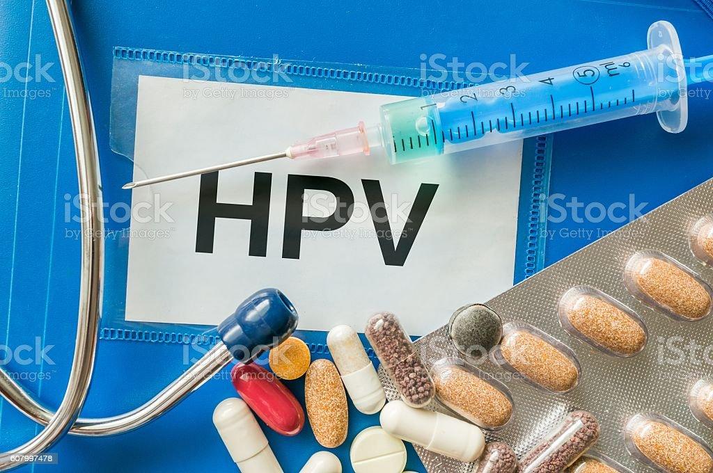 HPV virus desease concept. Many pills, syringe and stethoscope around. stock photo