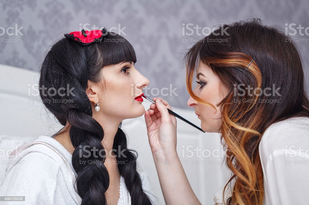 Visagist doing make-up bride. stock photo