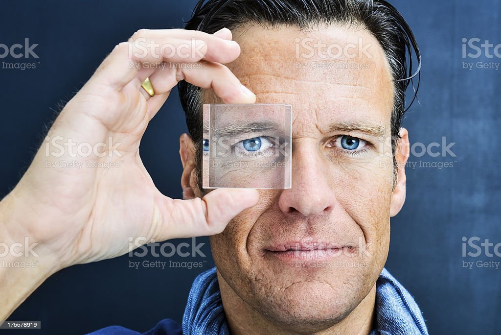 Vision: man looking through lens stock photo