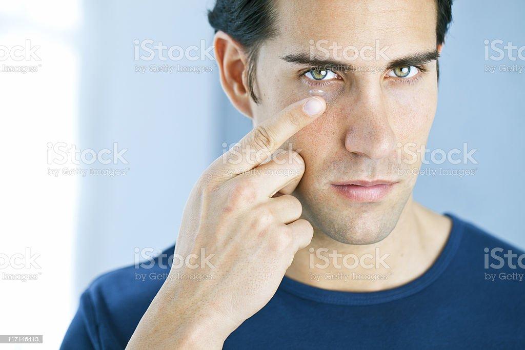Vision: man using a contact lens stock photo