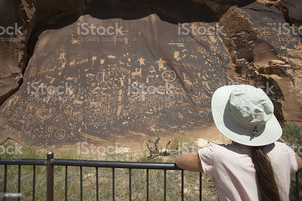 Visitor admires Newspaper Rock State Park petroglyphs Utah stock photo