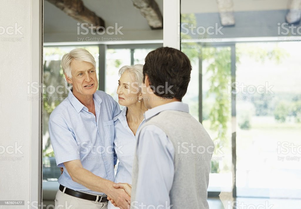 Visitor - Couple greeting a man at their door royalty-free stock photo
