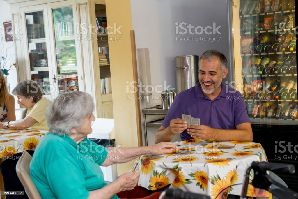 Visitor Playing Card With Senior Woman In The Nursery Home stock photo