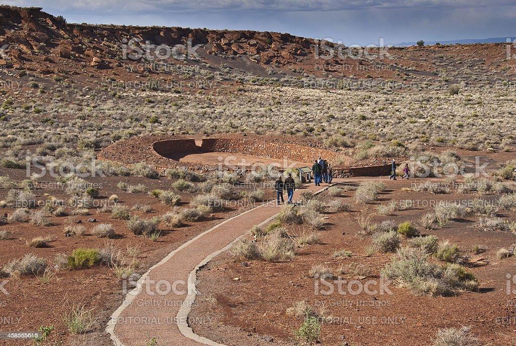 Visitors Walk to the Ball Court Near Wupatki Pueblo stock photo