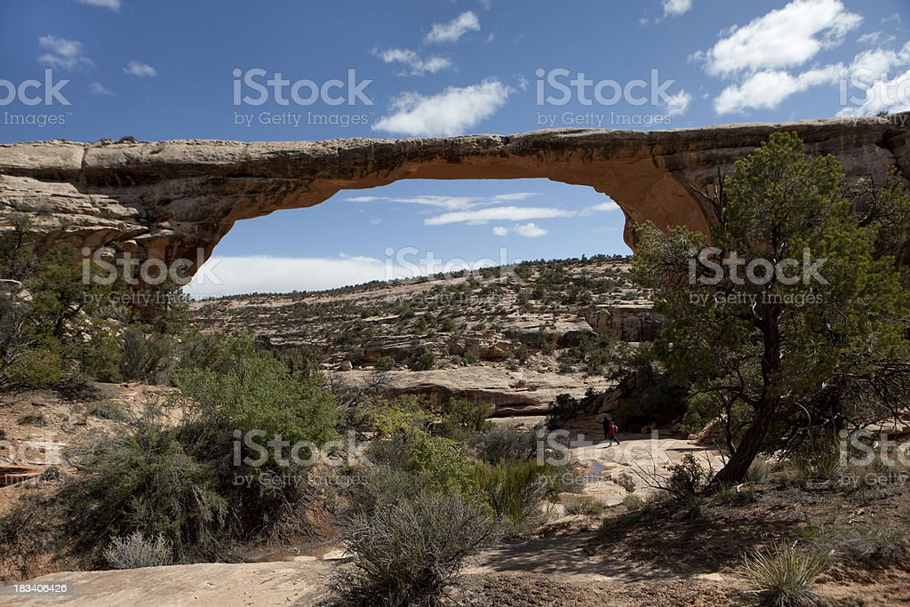 Visitors walk under rock archway in Natural Bridges NM Utah stock photo