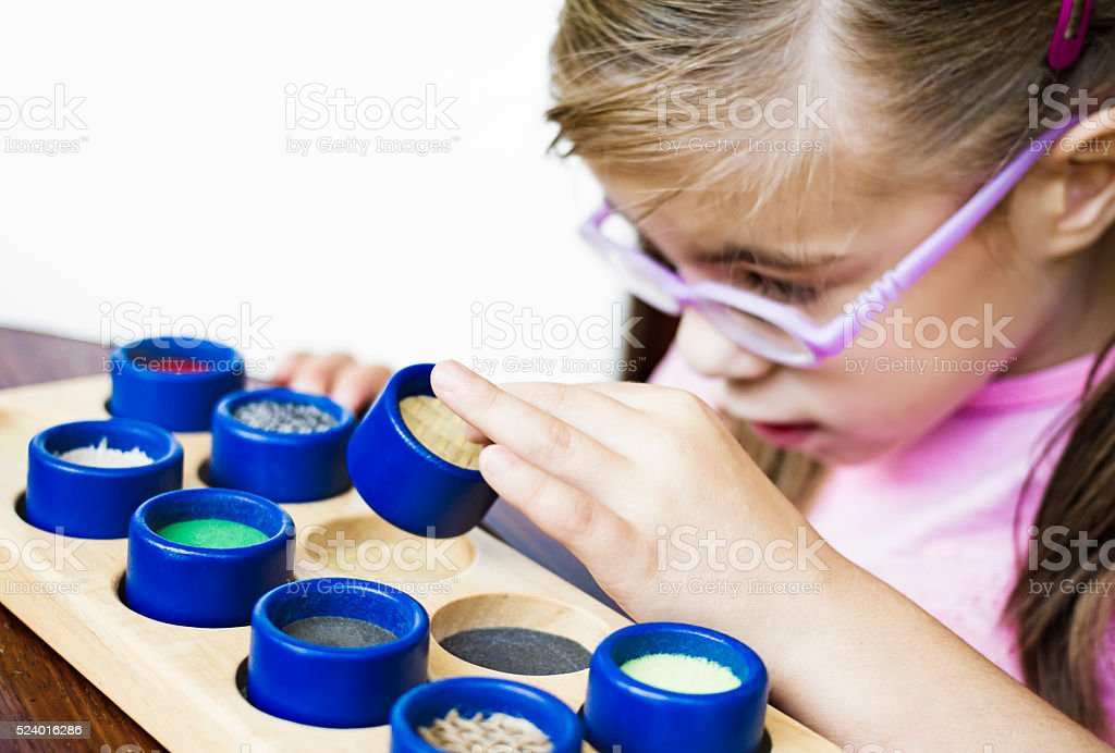 Visually disabled child playing with colorful textured rolls stock photo