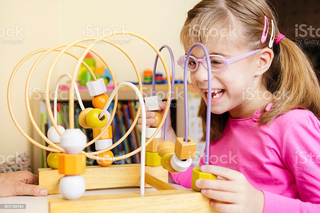 Visually disabled child playing with wooden roller coaster bead toy stock photo