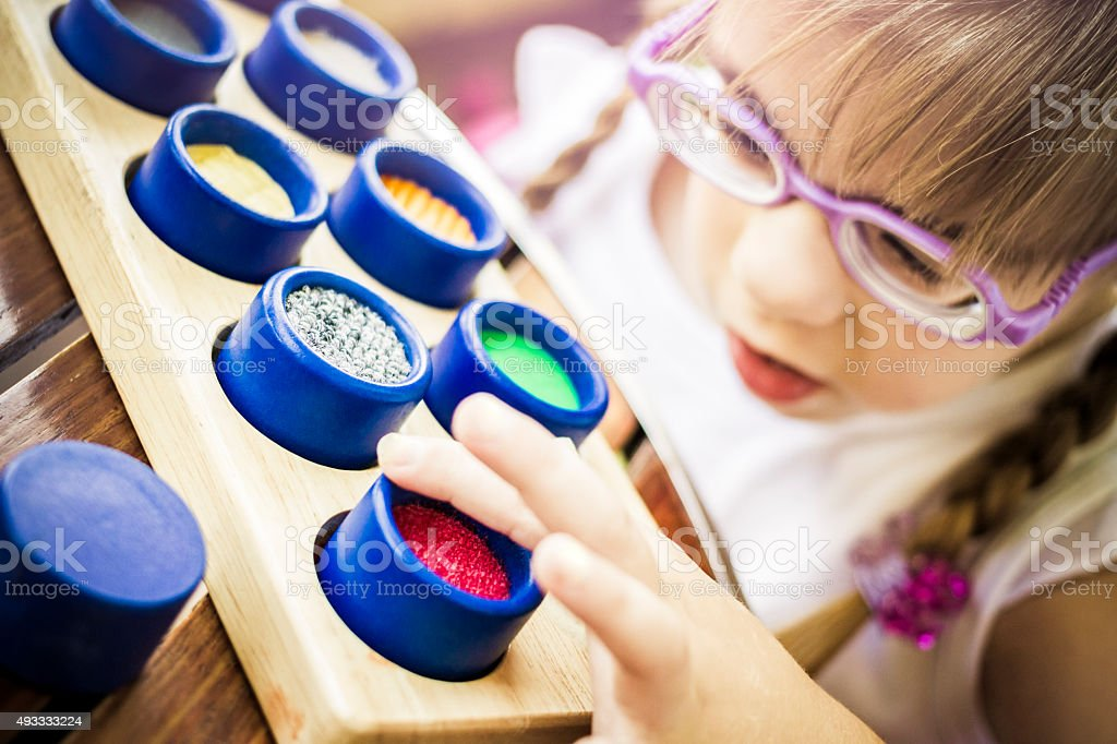 Visually disabled child with glasses playing on colorful textured rolls stock photo