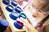 Visually disabled child with glasses playing on colorful textured rolls