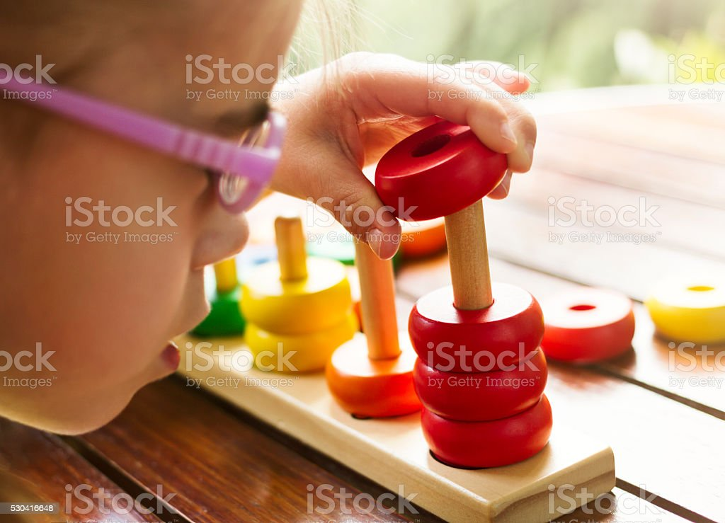 Visually disabled child with glasses playing with wooden stacking toy stock photo