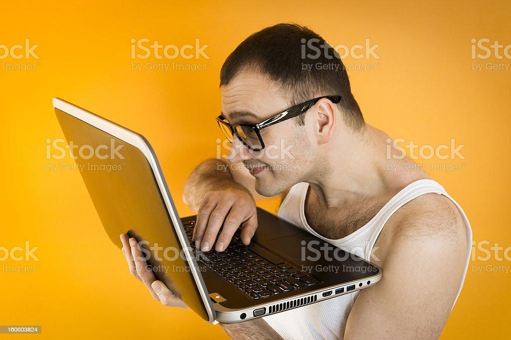 Visually impaired Nerd guy in sleeveless shirt working on laptop royalty-free stock photo