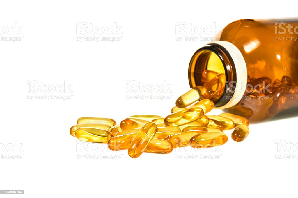 Vitamin D bottle with spilled contents isolated stock photo