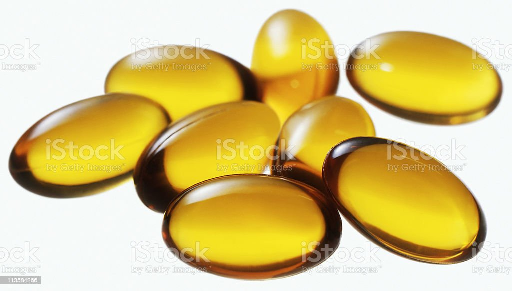 Vitamin e pills cut out on white stock photo
