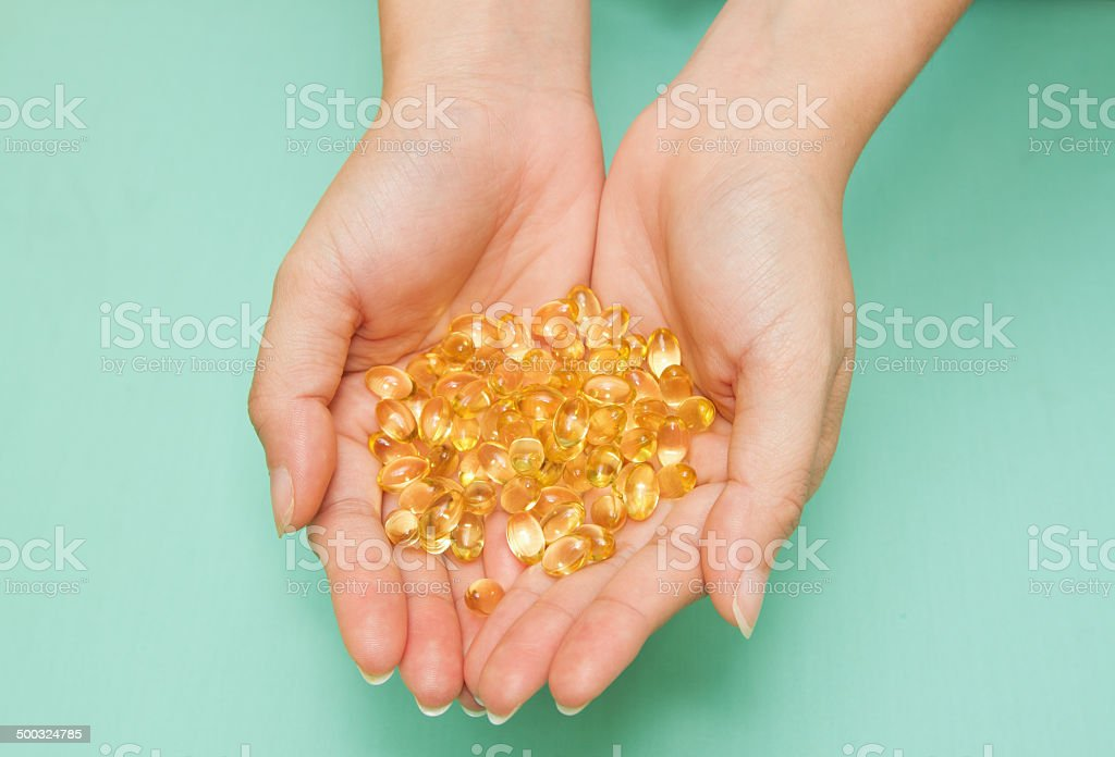Vitamin Omega-3 fish oil capsules on a hand stock photo