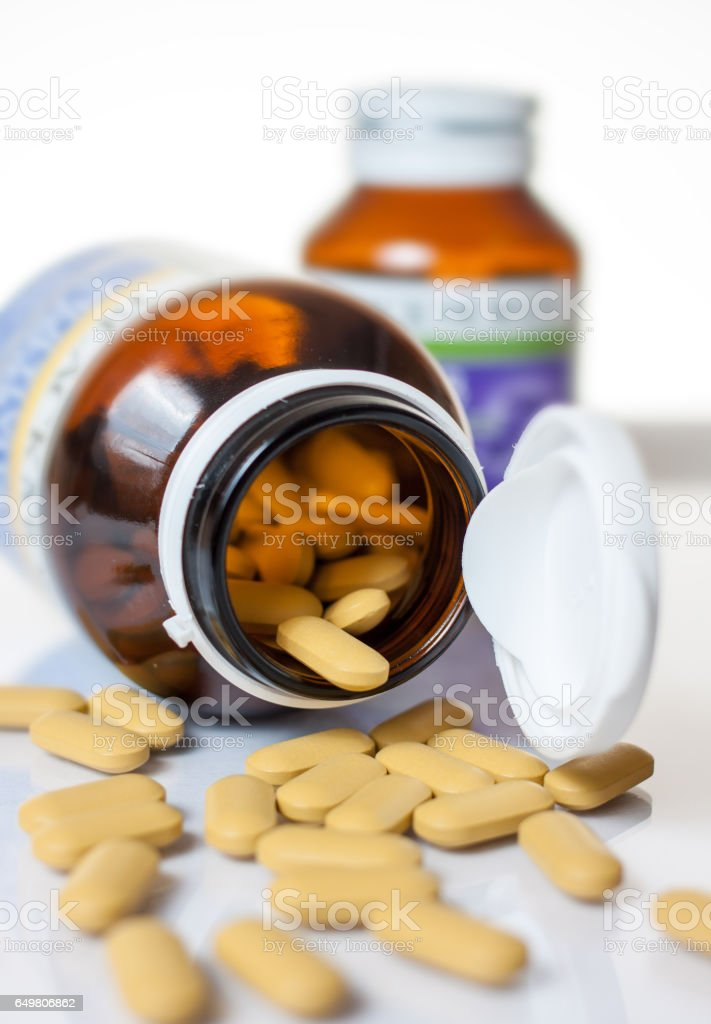 vitamin,Pills pouring out of the brown bottle stock photo