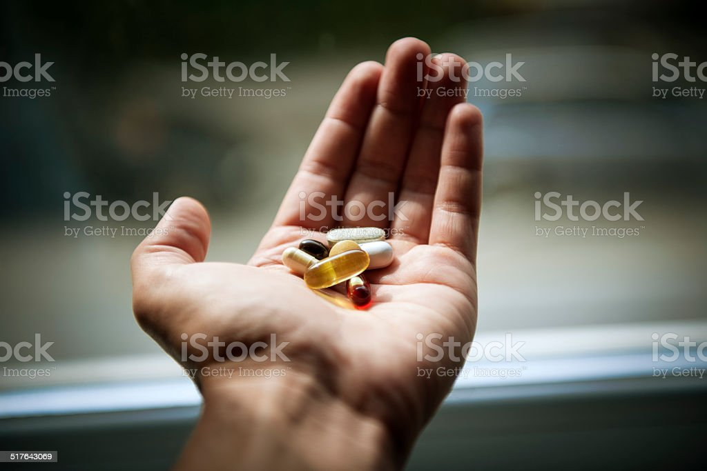vitamins and pills in man hand stock photo