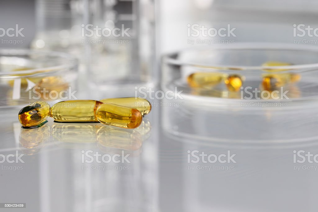 vitamins pills omega 3 supplements with petri dish stock photo