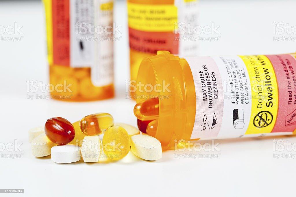 Vitamins spilling from prescription bottle stock photo