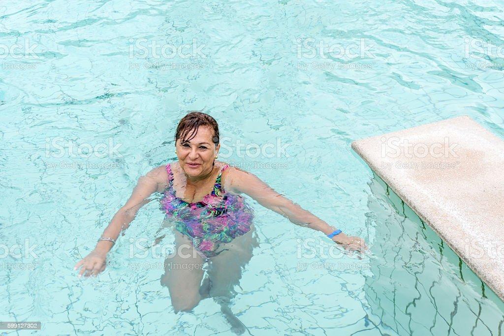 Vivacious senior smiling hispanic woman in swimming pool stock photo