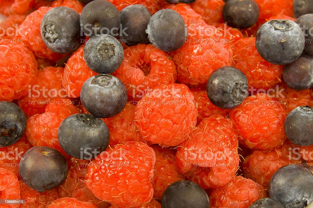 Vivid raspberries and blueberries royalty-free stock photo