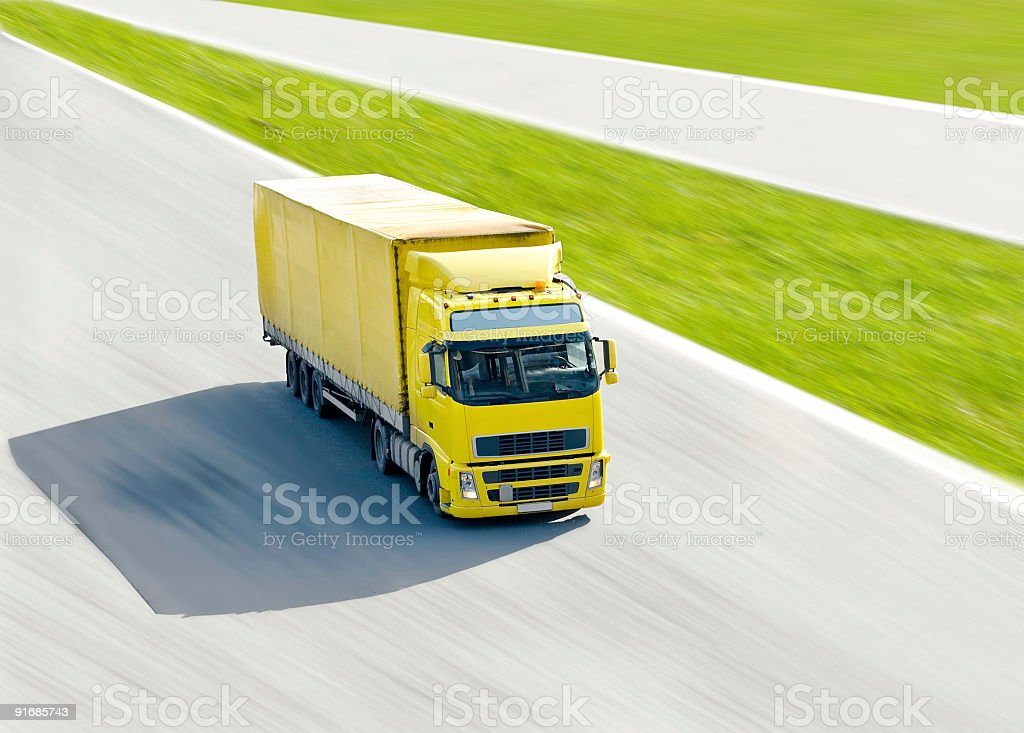 vivid yellow truck in motion under bright sun on  highway stock photo