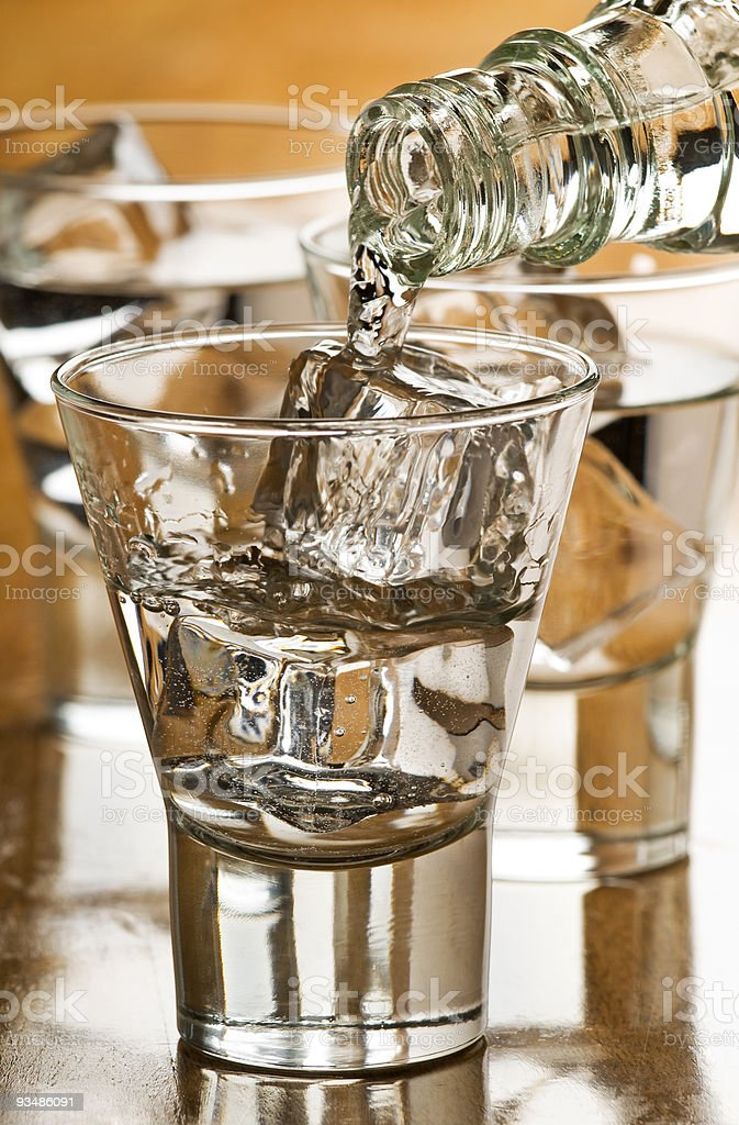 Vodka being poured into shot glasses over ice royalty-free stock photo