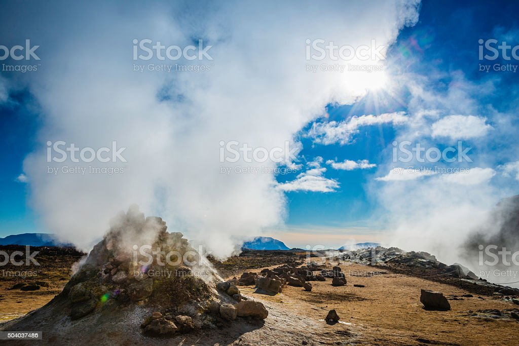 Volcanic vent shooting geyser steam in blue sky Hverir Iceland stock photo