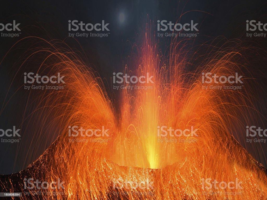 Volcano erupting at night stock photo