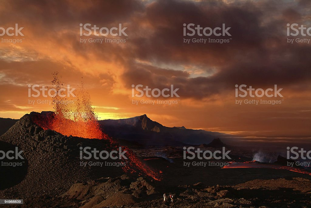 Volcano erupting at night spewing orange lava stock photo