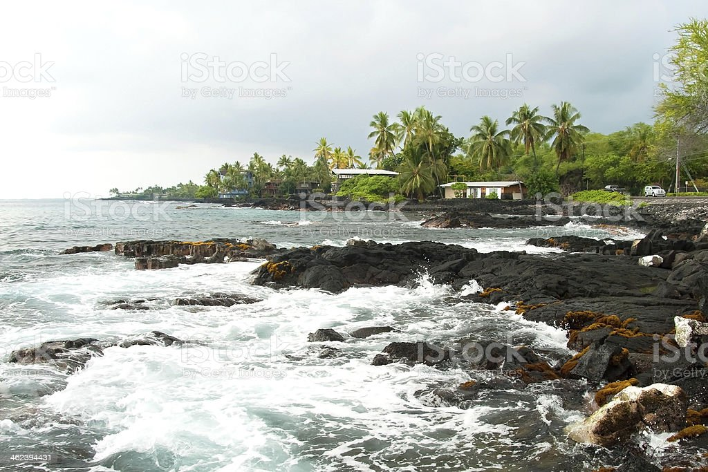 Volcano rocks with ocean and palm trees during storm royalty-free stock photo