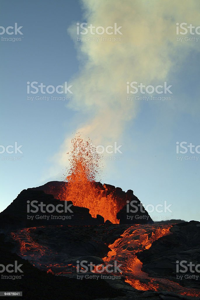 Volcano spewing lava out of a hole and running down stock photo