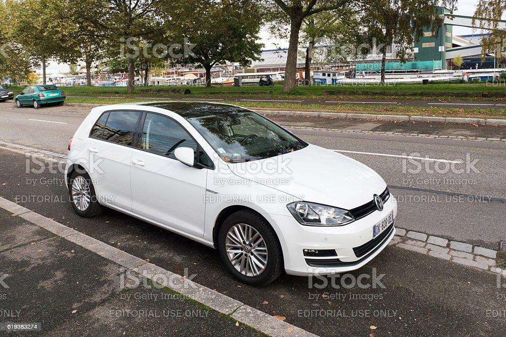 Volkswagen Golf white car parked on city street stock photo