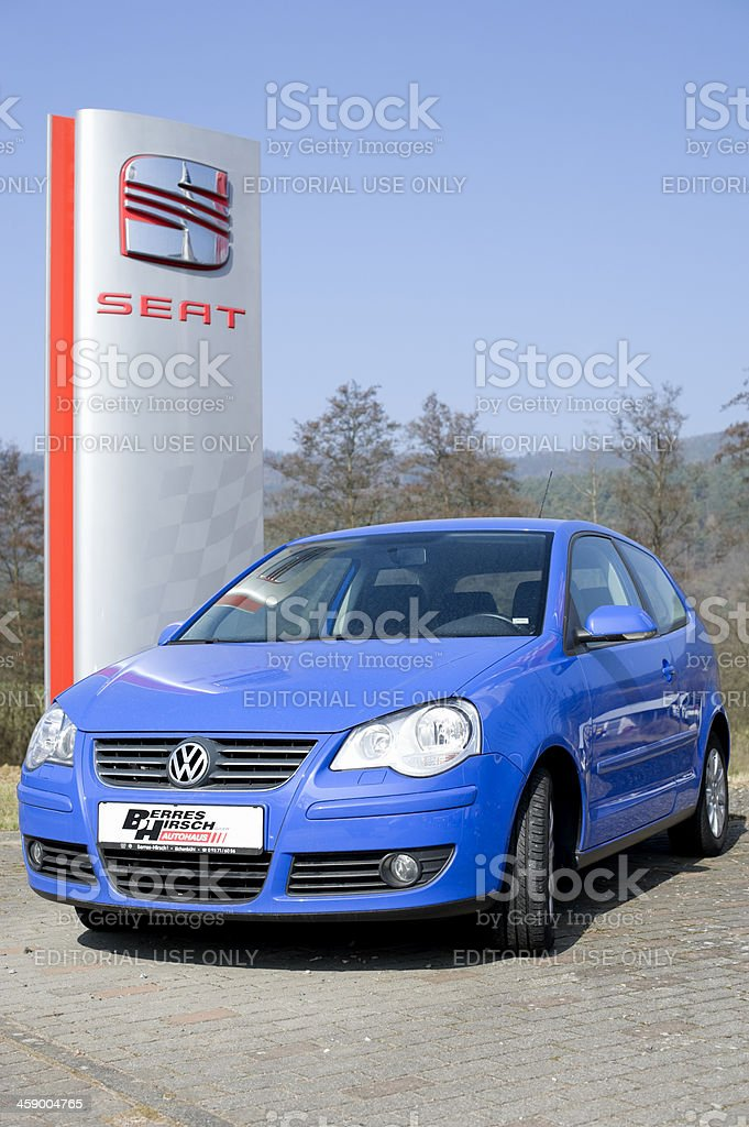 Volkswagen Polo in front of a Seat roadside sign royalty-free stock photo