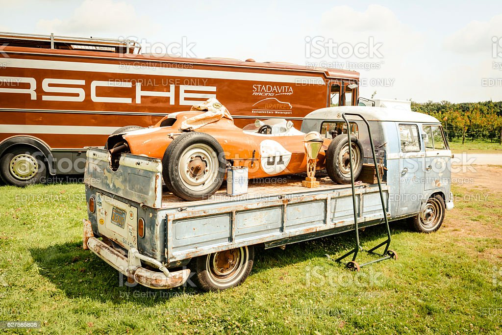 Volkswagen Transporter flatbed classic truck with a Porsche race car stock photo